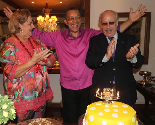 A alegria do aniversariante entre os anfitriões Cristina e Claudio Aboim