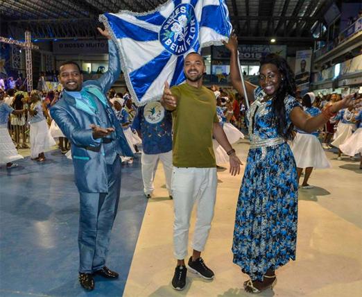 Jesse Williams ao lado de casal de mestre-sala e porta-bandeira